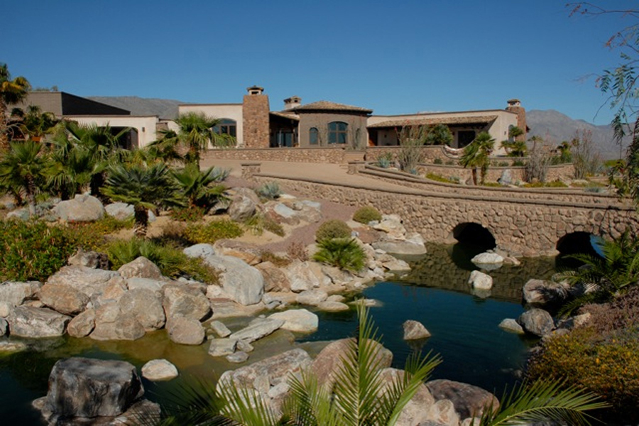 Strawbale home with water feature and desert plantings. Photo: Juergen Zierler.